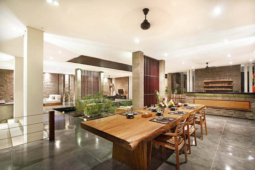 Kerobokan villa 310 - The large wooden table and plenty of day-beds throughout the common space to create a warm center for the group to unite
