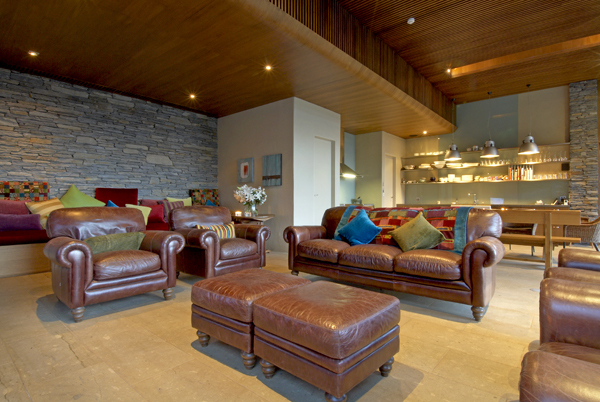 Queenstown Villa 649 - décor is a modern twist on 'cosy traditional' with several roll-arm leather chairs, sofas and ottomans upholstered in deep rich colours