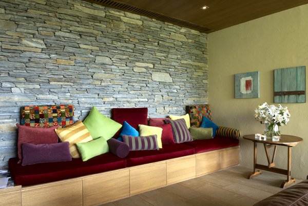 Queenstown Villa 649 - plush red velvet banquet along another stone wall complete with lots of cushions and bolsters for your comfort.