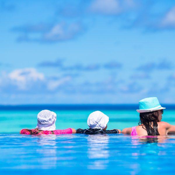Young beautiful woman and girls enjoying the luxurious quiet swimmingpool